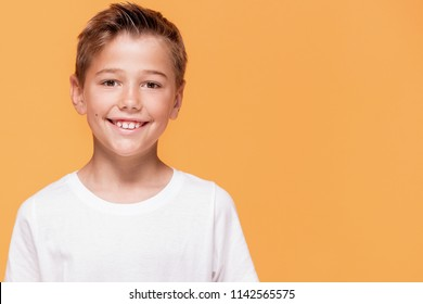 Happy little boy smiling to the camera. A lot of copy space , yellow studio background.