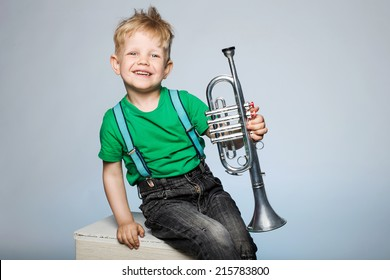 Happy little boy smiling and holding musical instrument