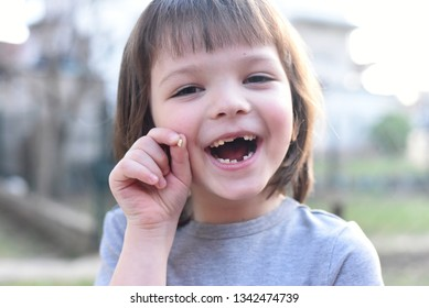 Happy little boy smiling and showing his missing teeth. Cute little boy lost first milk tooth.  Child showing his milk-tooth that has fallen