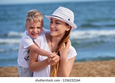 Happy little boy son hugs mother. Child loves mom,she looks away and smiles. Portrait young woman in hat together with cute blond kid having rest on beach. concept of holiday, vacation.