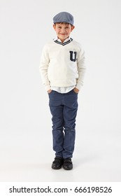 Happy little boy standing with hands in pockets over white background, looking at camera.
