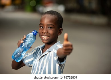 happy little boy standing with a plastic bottle and showing ok sign with thumb smiling
