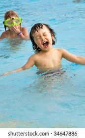Happy little boy in a  swimming pool.