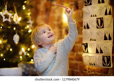 Happy little boy takes last sweet from advent calendar on Christmas eve. Traditional christmas calendar for kids