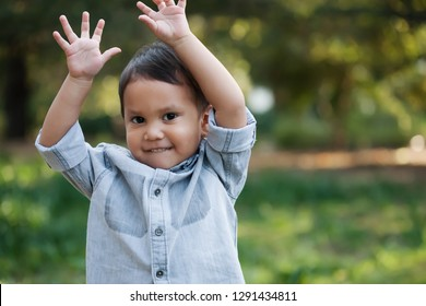 A happy little boy waving his hands up in the air, while standing in a green garden during spring.