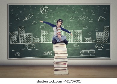 Happy little boy wearing helmet and sitting on a stack of books with picture at the chalkboard, shot in the class