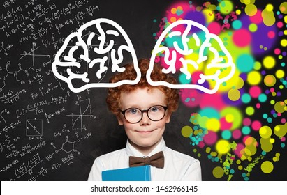 Happy little boy wearing white shirt and glasses standing near blackboard with colorful brain sketch hand drawn. Concept of creative thinking and education