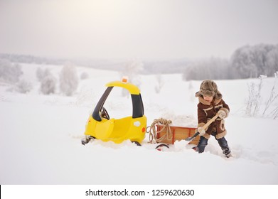 Happy little Boy in winter clothes.  The child is playing outside in the winter. A yellow toy car and a small cart filled with snow, stuck in the snow during the winter season. Snow removal.