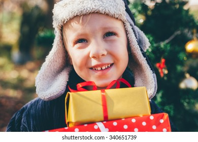 Happy little boy with winter hat and gifts