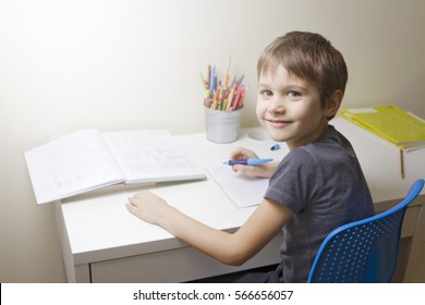 Happy little boy writting in notebook. Child sitting at the desk home and doing his homework. School, children, education concept