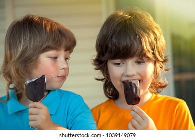 happy little boys eating an ice cream in summer outdoors.