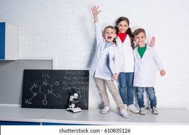 Happy little boys and girl in white coats looking at camera in chemical laboratory
