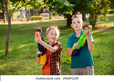 happy little boys playing with water guns