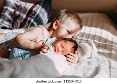 Happy little brother with newborn baby lying in a bed together, kissing and hugging. Siblings. New born baby and three years old brother together. Love. Family.