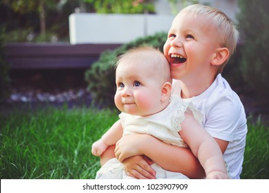 happy little brother playing hugs his sister baby sitting on grass in a green garden, concept of love and parenting.