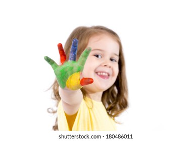 happy little caucasian girl 3-4 years old with hands painted in vivid colours isolated on white background