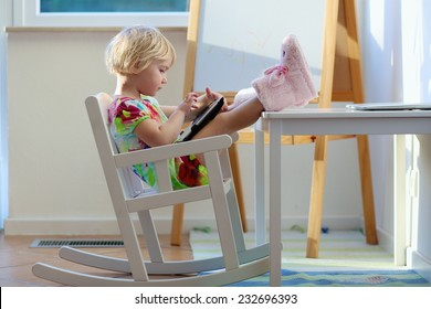 Happy little child, adorable blonde toddler girl enjoying modern generation technologies playing with tablet pc sitting comfortable indoors on a white rocking chair with her feet on the table