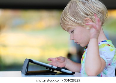Happy little child, adorable blonde toddler girl enjoying modern generation technologies playing indoors using tablet pc with touchscreen.