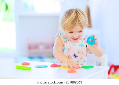 Happy little child, adorable creative toddler girl playing with dough, colorful modeling compound, sitting at white table in bright sunny room with big window at home or kindergarten