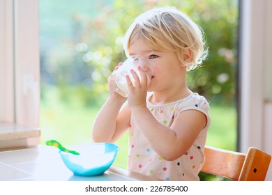 Happy little child, blonde curly toddler girl, enjoying healthy breakfast eating oatmeal porridge and drinking milk sitting in high chair at bright sunny kitchen next to big garden view window
