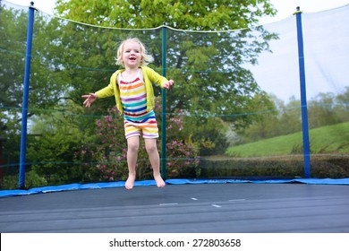 Happy little child, blonde curly toddler girl jumping on trampoline in the garden at the backyard of the house on a sunny summer day