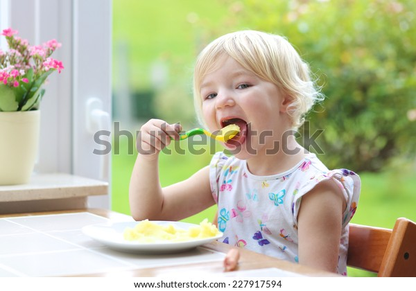 Happy little child, blonde curly toddler girl, enjoying healthy lunch eating mashed potatoes with sausage sitting in high chair at bright sunny kitchen next to big garden view window