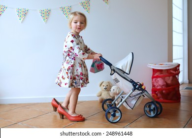 Happy little child, cute blonde toddler girl, wearing beautiful dress and red mom's shoes playing role game pushing stroller with baby doll indoors at home or kindergarten