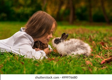 Happy little child girl with cute rabbit. Portrait of kid with pet. Outdoors.