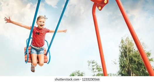 Happy little child girl laughing and swinging on a swing in the city park in summer