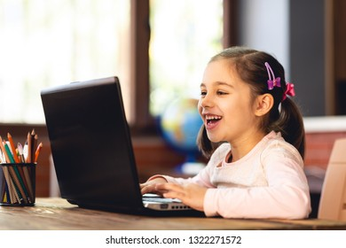 Happy Little Child Girl Using Laptop Computer and Typing on Keyboard in School