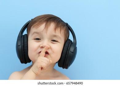 happy little child listening music with wireless headphones