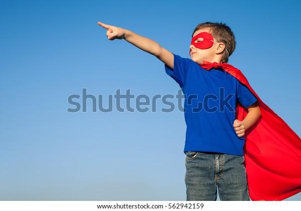 Niño feliz jugando superhéroe. Niño divirtiéndose al aire libre. Concepto de poder masculino.
