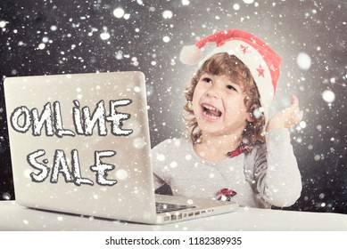 Happy little child with Santa hat and laptop computer,holiday online sale