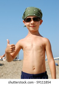 Happy little child with thumbs up at beach