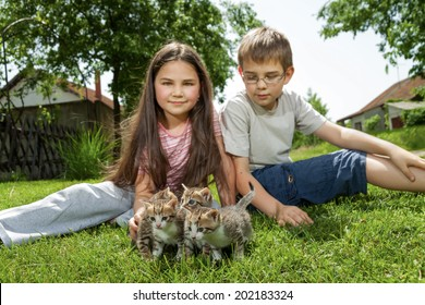 Happy little children with little cats outdoor playing