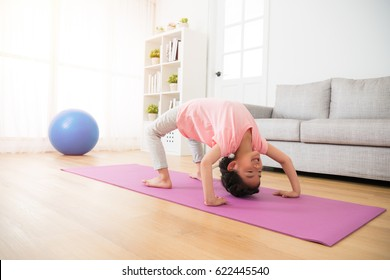 happy little children girl kid playing sports yoga fitness at home in front of a grey sofa in the room using legs and hand to holding up body on the mat.