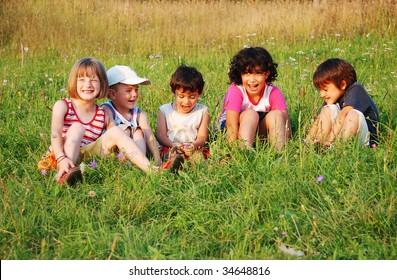 Happy little children in grass on meadow