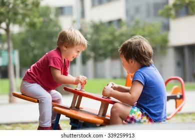 Happy little children having fun at city playground