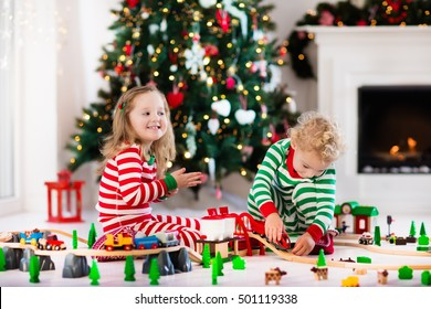Happy little children in matching pajamas playing with Christmas presents - wooden toy railroad and car. Family Xmas morning in decorated living room with kids gifts, fireplace and Christmas tree.