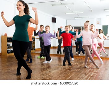 Happy little children studying modern style dance in class