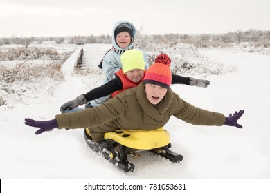 Happy little children with their mother in colorful clothes are pictured in front of a photographer on a sleigh. Scenic area with a bridge on the river. Winter vacation concept, Christmas, New Year