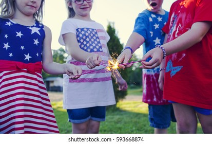 Happy little children wearing t-shirts and dresses with stars and stripes standing together, burning up Bengal lights and celebrating Independence Day