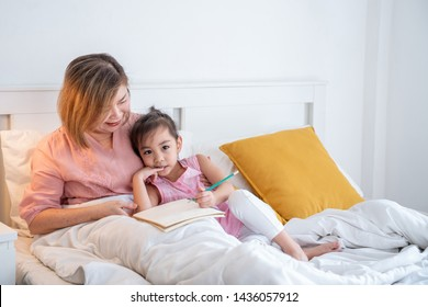 Happy little cute asian girl and her senior retired grandmother lying on the bed. Grandma smile and teach her preschool grandchild do homework or write on the book on the bed in bedroom.