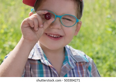 Happy little cute boy in glasses holds cherry at summer day outdoor, focus on berry