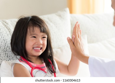 Happy little cute girl on consultation at the pediatrician. Girl is smiling and giving high five to doctor. Medicine and health care concept.