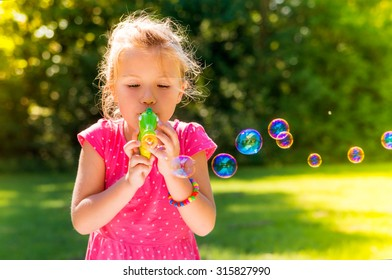 happy little cute kid blowing the spring