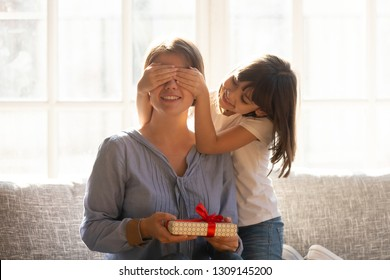 Happy little daughter covering mum eyes congratulating happy mom holding birthday present in gift box, smiling small kid girl making surprise to mommy on mothers day concept sitting on couch at home - Shutterstock ID 1309145200