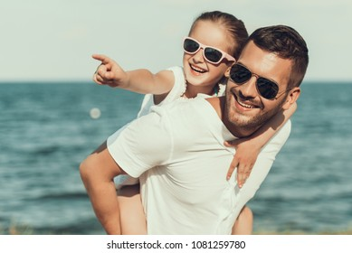 Happy little daughter in sunglasses sits on fathers back. Family on beach.