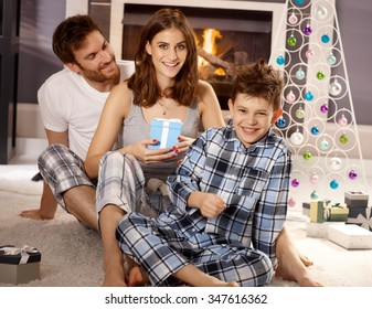 Happy little family at christmas morning, mother holding present, sitting on floor, having fun.