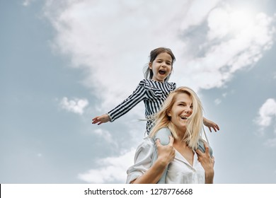 Happy little funny daughter on a piggy back ride with her happy mother on the sky background. Loving woman and her little girl playing in the park. Mom and kid has fun outside. Mother's day